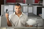 stock photo of pissed off  - Frustrated office worker with papers holds a phone away from his ear - JPG