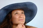 Portrait of a young woman in a blue sunhat with daydreaming romantic expression