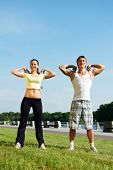 Young fitness couple of man and woman doing physical stretching exercises before jogging sport outdo
