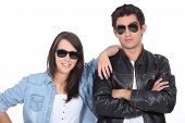 Young couple posing in sunglasses and leather jacket