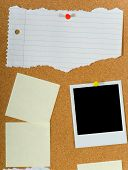 pic of bulletin board  - Bulletin board with assorted blank items including notes a torn sheet of paper and a blank instant transfer image or - JPG