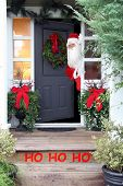 Santa Claus looking out of the front door of a home, beautifully decorated for Christmas.  poster