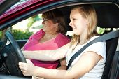 Teenage daughter gets a driving lesson from her mother or an instructor.