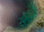 Aerial view of the karst lake named Goluboye Ozero (Blue Lake) surrounded by forest. Maximum depth i poster