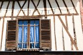 Window With Wooden Shutters And Blue Curtains In Old Half Timbered House