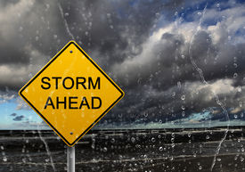 stock photo of warning-signs  - yellow warning sign of bad weather ahead against stormy sky - JPG