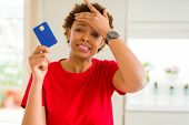 Young african american woman holding credit card stressed with hand on head, shocked with shame and  poster