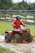 stock photo of four-wheelers  - Oncoming close up young adult female riding a 4 wheeler on a dirt road