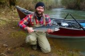 pic of steelhead  - A steelhead fisherman holds his trophy fish by his boat and the river in Oregon.