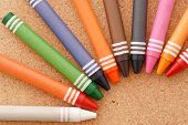 stock photo of daycare  - Fun Arrangements of jumbo Crayons on cork board surface for coloring and education concepts - JPG