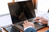 Businessman Or Broker Looking At Computer Laptop Analysing About Stock Market Invest Trading Stocks  poster