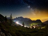 Milky Way above the mountains at night in summer. Landscape with alpine mountain valley, blue sky wi poster