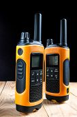 Two Walkie Talkie On Wooden Table On Dark Background poster