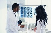 Two Doctors Look At An X-ray And Discuss The Problem. Medical Technicians Pointing At Mri X-ray Of P poster