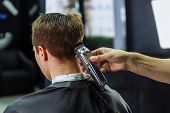 Male Haircut With Electric Razor. Barber Makes Haircut For Client At The Barber Shop By Using Haircl poster