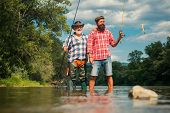 Happy Father And Son Together Fishing In Summer Day Under Beautiful Sky On The River. Fly Fishing. F poster