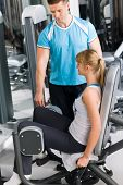 Young woman with personal trainer exercise legs at gym