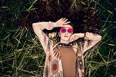 Portrait of a fashionable woman model lying on the grass. Modern Bohemian style. Spirit of freedom.  poster