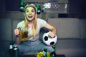 Young Woman Watch Football Game On Tv At Night. Cheerful Attractive Blonde Woman Hold Glass Of Beer  poster