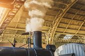 Vintage Steam Train At The Station. Steam From Steam Pipe Under The Arch Of The Station Roof poster