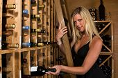 Beautiful Blond Picking A Bottle Of Wine