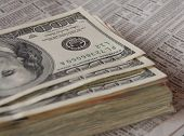 foto of financial management  - stack of money on newspaper financial page - JPG