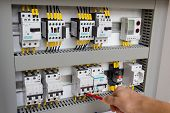 image of voltage  - Technician working at electrical cabinet  - JPG