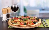 Deliciosa pizza com copo de vinho tinto e especiarias na mesa de madeira no fundo da sala