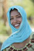 stock photo of dupatta  - Portrait of Muslim woman in blue headscarf smiling - JPG