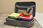pic of carry-on luggage  - Open grey suitcase with clothing on bed - JPG
