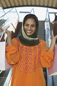 foto of dupatta  - Portrait of happy Indian female holding shopping bags with escalators in the background - JPG