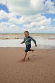 Happy Little Boy Running At The Sea Coast