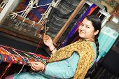 smiling young indian woman weaver working on loom manufacturing whool shawl clothing