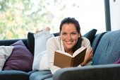 Smiling woman resting reading sofa learning leisure activity