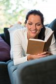Female student studying couch home bookworm woman living room