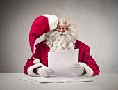Santa Claus reads sheets sitting at the desk