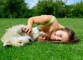 stock photo of puppy dog face  - beautiful young happy laugh girl playing with her dog outdoor - JPG
