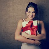 Portrait of attractive cheerful girl in sleeveless sports white shirt holding gift box with red bow