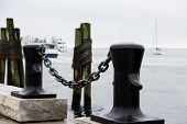 Black Bollards With Chain By Wood Pilings