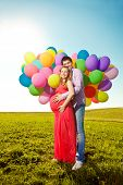 Young healthy beautiful pregnant woman with her husband and balloons outdoors. A Men  and girl with a tummy on the grass. Enjoyed by nature. Couple in love waiting for baby