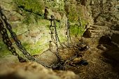stock photo of shackles  - Castle dungeon prison with chains chain and moss on stone walls - JPG