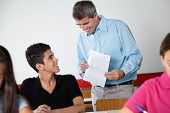 Happy male teacher and teenage schoolboy looking at paper during examination in classroom