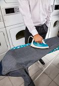 Low section of businessman ironing jeans in laundry