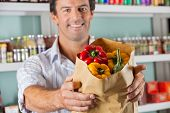 Portrait of mid adult male customer showing bellpeppers in paper bag at supermarket
