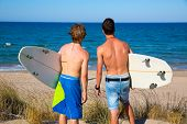 Boys teen surfers rear back view looking at beach from  dune