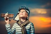 Boy with plane at sunset