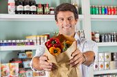 Portrait of happy man showing fresh bellpeppers in paper bag at grocery store