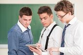 Three young students looking at a tablet pc