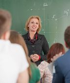 Smiling teacher on a blackboard listening to her students