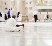 Muslim man sitting on ground and praying
